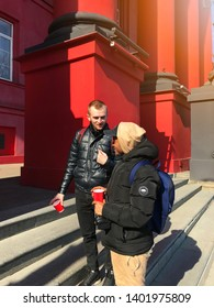 Kyiv, Ukraine - 03 03 2019: Two students staying on the stairs near Taras Shevchenko National University building talking and drinking coffee or tea in a red cups. White and black guys in jackets.