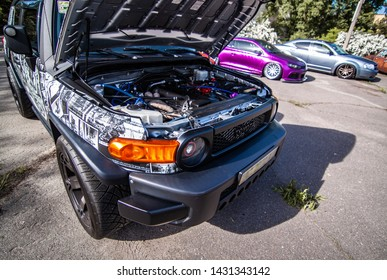 Kyiv, Ukraine - 18.05.2019 Tuned Toyota FJ cruiser with open hood on 1jz gte turbo engine and racing coloring. The SUV is at the festival of low cars.