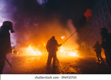 """Kyiv, Ukraine - 19 January, 2014: Fighter with flag of """"Ukrainian Insurgent Army"""" under a stream of water. Police use a water cannon, despite the freezing temperatures."""