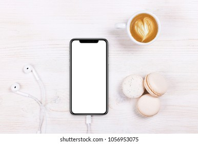 Kyiv, Ukraine, 2018-02-19. Coffee, cake macaron and phone X on white table from above. Flat lay style.