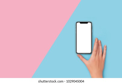 Kyiv, Ukraine, 2018-02-19. Girl holding  iPhone X  on pink and blue background