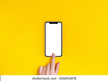 Kyiv, Ukraine, 2018-02-19. Top view of a woman hand using phone on yellow background.