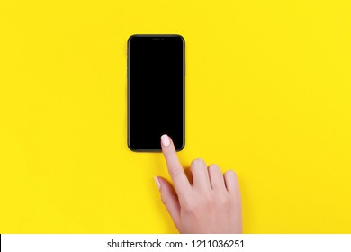 Kyiv, Ukraine, 2018-10-19. Top view of a woman hand using iphone XS on yellow background.
