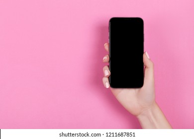 Kyiv, Ukraine, 2018-10-19. Top view of a woman hand using iphone XS on pink background.
