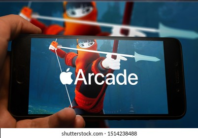 Kyiv/ Ukraine/ 25.09.2019: Hand holding phone with Apple Arcade logo displayed in it with fluctuating graphic on background.