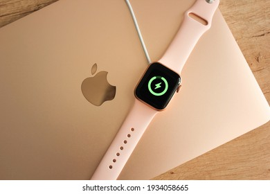 Kyiv, Ukraine — 5 March 2021: Apple Watch 40mm gold with pink bracelet is charged by magnetic charging, accompanied by a green charging indicator.  Apple Watch lie on a wooden table and on a MacBook.