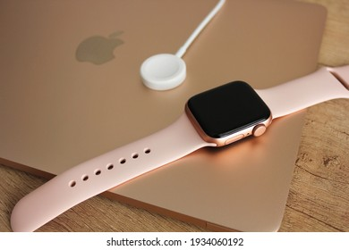 Kyiv, Ukraine — 5 March 2021: Apple Watch 40mm gold with pink bracelet is next to the magnetic charger.  Apple Watch lie on a wooden table and on a MacBook laptop 12 diagonal gold