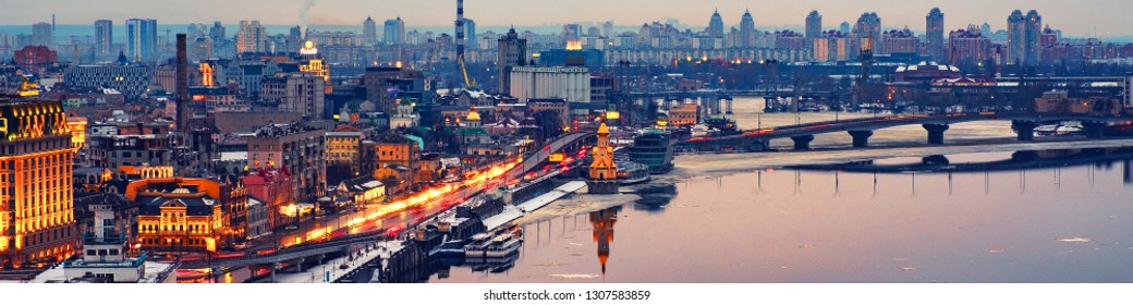 Kyiv, Ukraine. Aerial view of Podol and Dnipro river in the evening in Kyiv, Ukraine. Modern buildings and car traffic