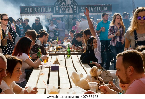 KYIV, UKRAINE - APR 17: Crowd of hungry people eating meals around tables outdoor during Street Food Festival on April 17, 2016. Kiev is the 8th most populous city in Europe.
