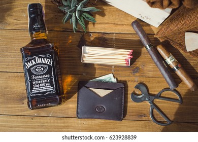 KYIV, UKRAINE - APRIL 01, 2017: Bottle of Jack Daniel's on the table with succulent and cigars, men's wallet, dollars and matches.