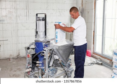 KYIV, UKRAINE - April, 03, 2019: Contractor making plaster concrete with plastering machine for house plastering walls. Electric Spray Plaster Machine. Automatic cement wall screeding plaster.