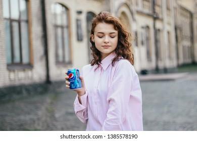 KYIV, UKRAINE - APRIL 04, 2019:Happy girl drink Pepsi