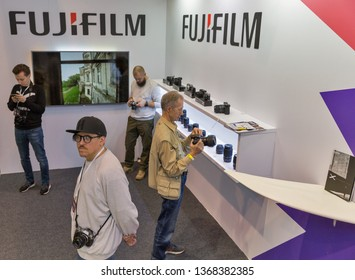KYIV, UKRAINE - APRIL 06, 2019: People testing professional photographic cameras on FujiFilm company booth during CEE 2019, the largest consumer electronics trade show of Ukraine in Tetra Pack EC.