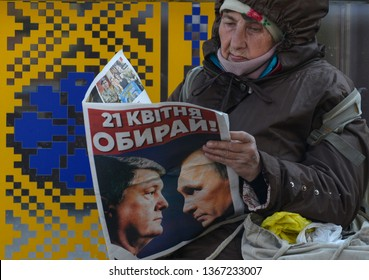 KYIV, UKRAINE- April 10, 2019:An elderly Ukrainian woman reads a pre-election leaflet of President Poroshenko's  with the image of the President of Ukraine Petro Poroshenko and the President of Russia