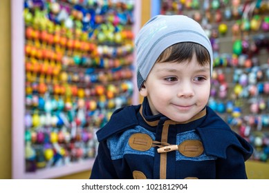 KYIV, UKRAINE APRIL 9, 2017: Several Easter colored eggs hanging on a wall color sunny spring day. Easter traditional egg exhibition. Boy portrait