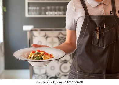 KYIV, UKRAINE - AUG 15: Waiter in uniform hurry to bring customers hot plate of tasty pasta inside modern restaurant on August 15 2018. Kiev is cultural centre of Eastern Europe with 3 millions people