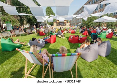 KYIV, UKRAINE - AUG 19: Many people sitting in shadows, relaxing in loungers on grass during popular outdoor Street Food Festival on August 19, 2017. Kiev is the 8th most populous city in Europe