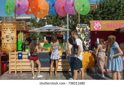 KYIV, UKRAINE - AUG 19: Young women buying cold drinks and fast food at outdoor pop-up cafe during Street Food Festival on August 19, 2017. Kiev is the 8th most populous city in Europe.