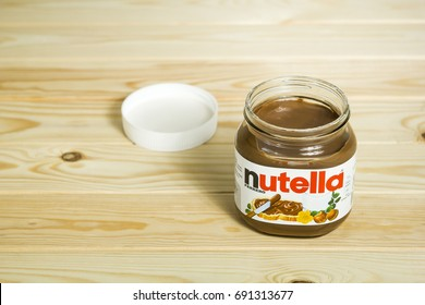 Kyiv, Ukraine - Aug 5th, 2017: Jar of Nutella Hazelnut. Opened jar with a nutella on a wooden background.