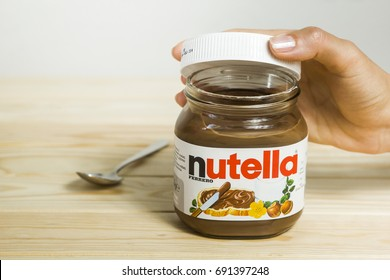 Kyiv, Ukraine - Aug 5th, 2017: Jar of Nutella Hazelnut. A female hand opens a jar with a nutella. Nutella on a wooden background.