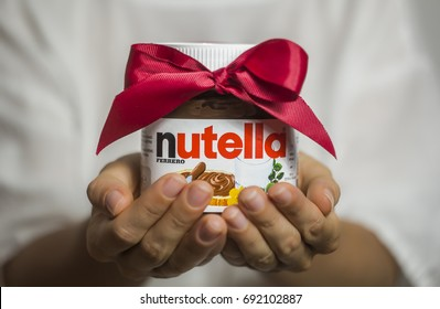 Kyiv, Ukraine - Aug 5th, 2017: Jar of Nutella Hazelnut. Woman giving chocolate cream bandaged with bow. Gift.