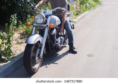 Kyiv, Ukraine - August 2019 : Man starts motorcycle with engine key.