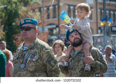Kyiv, Ukraine - August 24, 2019: Happy Ukrainian soldier in military uniform ride his cheerful daughter on neck during march of Ukrainian veterans of Russian-Ukrainian war on Independence Day