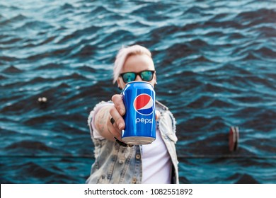 Kyiv, Ukraine - August 25, 2017: A happy young girl with pink hair is holding a can of Pepsi