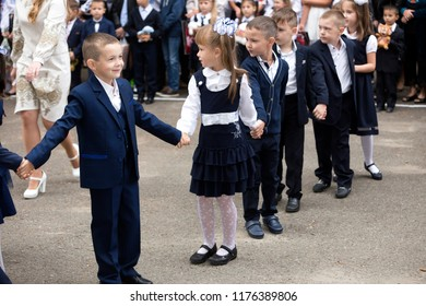 KYIV, UKRAINE - August 25, 2018: 1 September, day of knowledge celebration. Smiling happy first graders entering sunny schoolyard holding hands on blurred sunny schoolchildren and parents background.