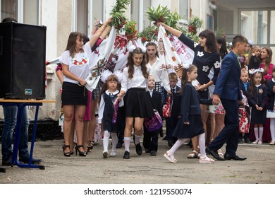 KYIV, UKRAINE - August 25, 2018: 1 September, School day of knowledge celebration. Schoolchildren, first graders entering sunny schoolyard led by hand, greeted by parents with flowers and teachers.