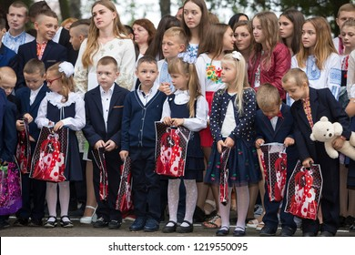 KYIV, UKRAINE - August 25, 2018: Schoolchildren in uniforms, first graders with present packages and soft toys, parents and teachers in sunny schoolyard on 1 September, day of knowledge celebration.