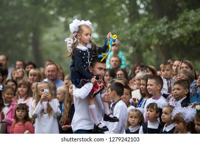 KYIV, UKRAINE - August 25, 2018: 1 September, knowledge day celebration. Cute first grader girl rings school bell sitting on senior pupil shoulder on happy parents and green trees blurred background.