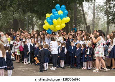 KYIV, UKRAINE - August 25, 2018: Schoolchildren boys and girls in uniforms, embroidered shirts, first graders with blue and yellow balloons, parents and teachers in schoolyard on 1 September.