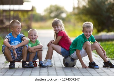KYIV, UKRAINE - August 25, 2018: Group of cute happy funny laughing young children, three boys and pretty long-haired girl sitting on skateboard and soccer ball on sunny pavement blurred background.