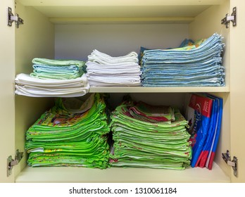 KYIV, UKRAINE - August 25, 2018: Interior of white plastic cabinet or clothing wardrobe with open doors with stacked pile of clean colorful linen. Household and order, furniture design concept.
