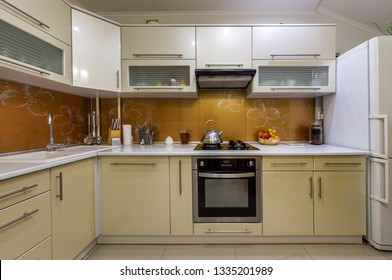 KYIV, UKRAINE - August 25, 2018: Interior of modern kitchen with all appliances. Tiled floor and walls, teapot on stove top, marble counter with kitchen utensils, white cabinets and fridge.