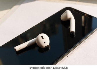 KYIV, UKRAINE - AUGUST 28, 2018: white Apple AirPods lie on a dark black surface of iPhone