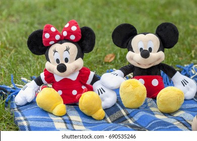 KYIV, UKRAINE - August 5, 2017: the figure of Mickey Mouse and Minnie Mouse from the Disney character. This character from the animation series of the mouse and Mickey's friend sit on the grass