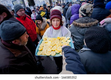 KYIV, UKRAINE - DEC 8: Woman treats demonstrators lemons in the crowd of people on the occupying street during two weeks anti-government protest on December 8, 2013, in Kiev, Ukraine.