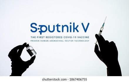 "Kyiv, Ukraine - December 03, 2020: Backlit single shot image of Sputnik V logo on tv screen  with a hand holding an ""Gam-COVID-Vac"" Covid-19 vaccine concept."