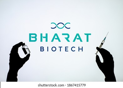 Kyiv, Ukraine - December 03, 2020: Backlit single shot image of Bharat Biotech logo on tv screen  with a hand holding an Covid-19 vaccine concept.