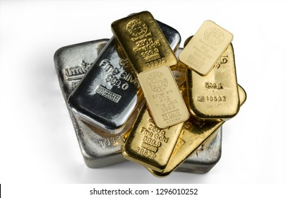 Kyiv, Ukraine - December 05, 2018: A pile of gold and silver bars from different manufacturers lies on a white background.