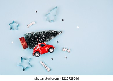 KYIV, UKRAINE - December 12, 2017: Toy red car with fir tree on the roof. Blue pastel background. Flat lay style. Concept of celebrating new year. Christmas mood.