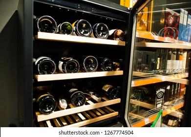 Kyiv, Ukraine - December 19, 2018: Bottles of different wines on shelves in fridge at supermarket.