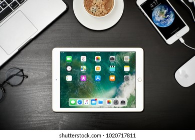 Kyiv, Ukraine - Fabruary 6, 2018: Apple iPad Gold with iPhone 8 plus and MacBook Pro on black table, top view. Apple Inc. is an American multinational corporation that develops consumer electronics