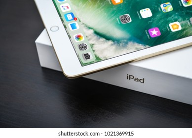 Kyiv, Ukraine - Fabruary 6, 2018: Brand new white Apple iPad Gold with box on black wooden background closeup, 7th generation of the iPad, developed by Apple inc. and was announced on March 21, 2017