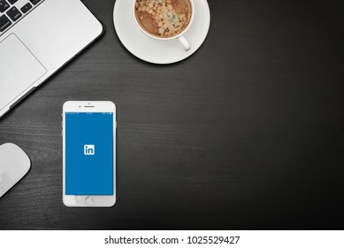 Kyiv, Ukraine - Fabruary 6, 2018: Apple iPhone 8 plus with Linkedin app on the screen on black desk with headphones, MacBook and iPad, top view. Linkedin is a social networking website