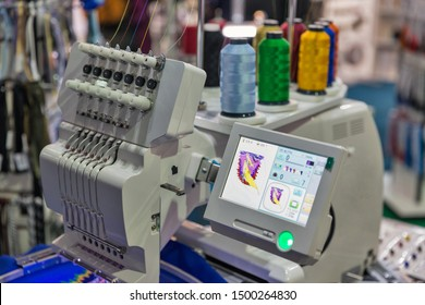 KYIV, UKRAINE - FEBRUARY 07, 2018: Modern professional machine for applying embroidery on different tissues with display and colorful reels of threads closeup.