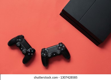 Kyiv, Ukraine - February 07 2019: the sony dualshock controller for PlayStation 4 On a coral color background. Top View.