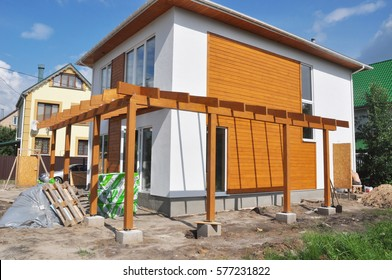 KYIV - UKRAINE, FEBRUARY - 12, 2017:  House construction. Contemporary Outdoor Terrace. Modern Home Construction with wooden pillars terrace patio installation. Building new modern house.
